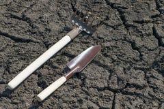 Садовые инструменты сгребают и копают ложь на треснутой земле в предыдущей весне в саде стоковое фото rf