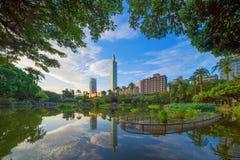 Сад парка Тайбэя и отражение зданий небоскребов Финансовые район и деловые центры в умном городском городе в полдень, стоковая фотография rf