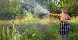 Сад шланга мальчика на летний день стоковое изображение rf