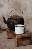 Сажный старый чайник и белая эмаль mug на малом деревянном стенде Стоковое Изображение