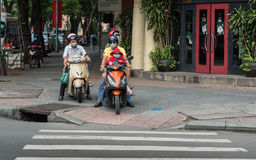 Сайгон, Вьетнам - семья с лицевыми щитками гермошлема на катании самоката на мостоваой Стоковая Фотография