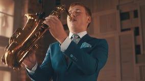 Саксофонист в голубом джазе игры костюма на золотом саксофоне с микрофоном элегантность видеоматериал