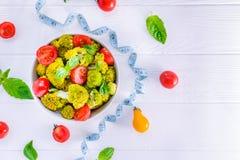 Салатница с томатами вишни, брокколи взгляд сверху, свежие ингридиенты, измеряя лента на белой деревянной предпосылке здоровая жи Стоковые Фотографии RF