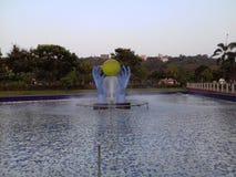 Салатовый большой шарик окруженный очень большими голубыми руками в воде стоковые изображения rf