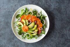 Салат апельсина крови авокадоа над смешанными зелеными цветами стоковые фотографии rf