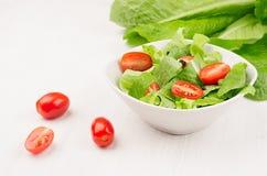 Салат весны свежий зеленых кусков томата шпината и вишни в белом шаре на белой деревянной предпосылке, крупном плане, космосе экз Стоковое Изображение