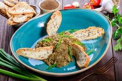 Салат испек баклажан с зелеными луками, чесноком, травами, гренками и томатами на темной деревянной предпосылке Стоковое фото RF