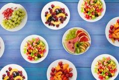 салат померанца кивиа плодоовощей плодоовощ диетпитания банана яблока Плоды на плите на деревянной предпосылке еда здоровая стоковые фото