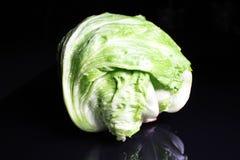 Салат салата айсберга Весь зеленый салат салата айсберга на черной отражательной предпосылке студии черное сияющее зеркало зеркал Стоковая Фотография RF