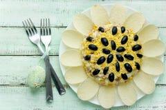 Салат солнцецвета украшенный с картофельными стружками, мозолью, яичком и оливкой Стоковые Фото