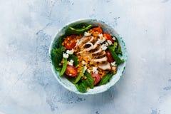 Салат с красными чечевицами, листьями шпината, томатами вишни, мясом цыпленка и сыром chella моццареллы с оливковым маслом в кера стоковое изображение
