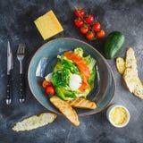 Салат цезаря с яичком, семгами, авокадоом, томатами вишни и зажаренной здравицей на серой предпосылке Плоское положение, взгляд с Стоковое Изображение RF