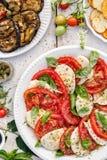 Салат Caprese сделанный отрезанных свежих томатов, сыра моццареллы и базилика служил на белой плите на деревянном столе стоковое фото