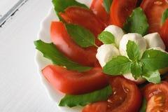 Салат Caprese с зрелыми томатами и сыром моццареллы при свежие листья базилика изолированные на белой предпосылке красивейшие дет Стоковая Фотография