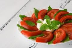 Салат Caprese с зрелыми томатами и сыром моццареллы при свежие листья базилика изолированные на белой предпосылке красивейшие дет Стоковые Фотографии RF