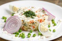 Салат Olivier с форелью в белой плите традиционное тарелки русское Деревянная предпосылка стоковые фотографии rf