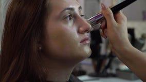 Салон красоты Молодая красивая модель девушки сидит в стуле Визажист делает макияж девушки Визажист акции видеоматериалы