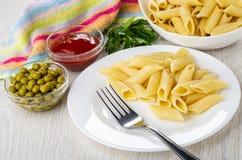 Салфетка, петрушка, плита с макаронными изделиями, шары с кетчуп и зеленые горохи, макаронные изделия, вилка в плите на деревянно стоковое изображение rf