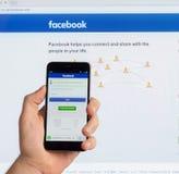Самая большая американская социальная сеть в мире Facebook на экране китайского телефона Xiaomi в мужской руке и на co Стоковое Изображение
