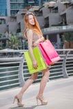 Самая лучшая покупка Маленькая девочка держа хозяйственные сумки и смотря в s Стоковое Изображение