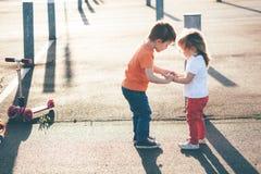 Самокаты езды брата и сестры Заход солнца Стоковое Изображение