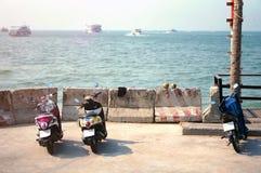 Самокаты припаркованные на автостоянке с заливом моря Стоковые Изображения RF