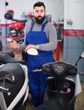 Самокаты работника человека предлагая в мастерской мотоцикла Стоковая Фотография