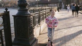 Самокат езды маленького ребенка в парке на летний день Милая игра девушки outdoors Активный отдых и внешний спорт для детей акции видеоматериалы