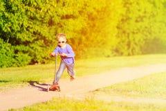 Самокат катания мальчика в парке лета Стоковая Фотография