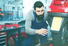 Самокат мужского работника фиксируя неудачный в мастерской Стоковое Изображение