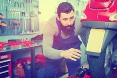 Самокат мужского работника фиксируя неудачный в мастерской Стоковые Фотографии RF