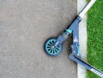 Самокат пинком лежит на краю дороги Стоковое Фото