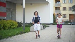 Самокат пинком катания девушки и мальчика outdoors Счастливые милые дети играя на улице уча сбалансировать на доске пинком акции видеоматериалы