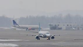 Самолеты двигая в авиапорт Мюнхена, зимнее время с снегом видеоматериал