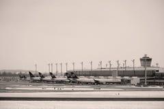 Самолеты на терминальных стробах в авиапорте Мюнхена, зимнем времени с снегом Стоковые Изображения RF