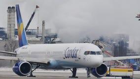Самолет в авиапорте Мюнхена, взгляд кондора конца-вверх после размораживать