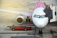 Самолет в аэропорте обслуживаемом наземной командой Нагружая груз в воздушные судн перед отклонением Подготовка самолета стоковое фото