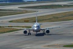 Самолет ездя на такси на взлетно-посадочной дорожке аэропорта стоковое фото