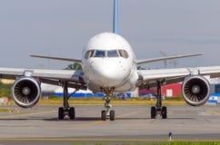 Самолет ездя на такси на рисберме авиапорта на асфальте видимая маркировка стоковая фотография