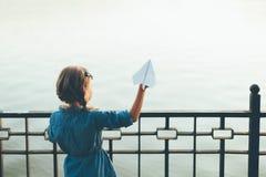 Самолет игрушки девушки запуская бумажный смотря к озеру Стоковые Изображения