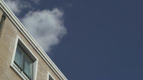 Самолет летает далеко в небо над домом акции видеоматериалы