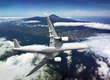 Самолет летая над островом стоковые фото