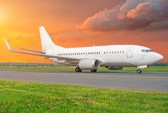 Самолет пассажира ездя на такси к взлётно-посадочная дорожка на небе авиапорта красивом на заходе солнца Стоковое Изображение