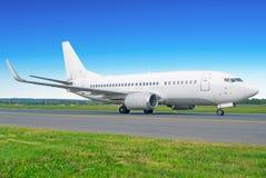 Самолет пассажира ездя на такси к взлётно-посадочная дорожка на авиапорте Стоковые Фотографии RF