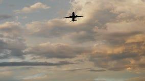 Самолет пассажира принимая на заход солнца на фоне очень красивые облака стоковые фото
