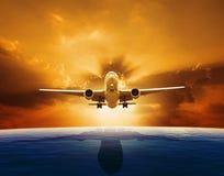 Самолет пассажирского самолета летая над красивым уровнем моря с комплектом солнца стоковые фото