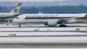 Самолет Сингапоре Аирлинес на взлётно-посадочная дорожка в авиапорте Мюнхена, Германии, зимнем времени с снегом видеоматериал