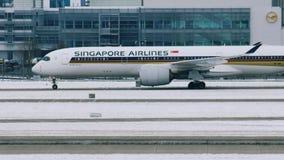 Самолет Сингапоре Аирлинес на взлётно-посадочная дорожка в авиапорте Мюнхена, Германии, зимнем времени с снегом сток-видео