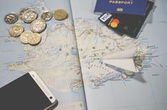 Самолет, смартфон, биометрический паспорт, доллары, монетки и кредитные карточки лежат на карте стоковое фото rf