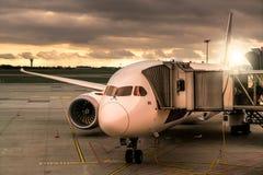Самолет стоит с тоннелем на авиапорте на заходе солнца стоковое фото